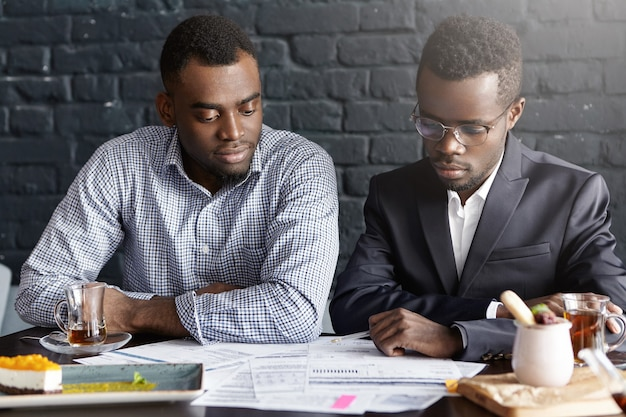 Deux professionnels afro-américains ayant une réunion officielle au bureau moderne