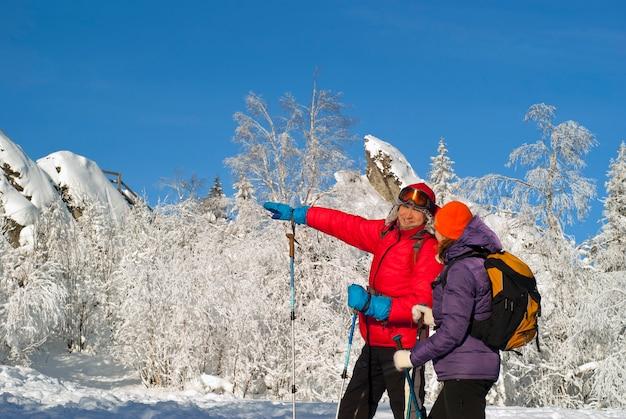 Deux randonneurs en hiver par une claire journée glaciale sur fond de forêt enneigée et de rochers