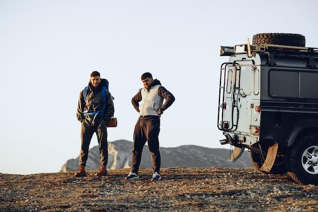 Deux randonneurs hommes debout près de voiture tout-terrain se préparant à commencer leur voyage