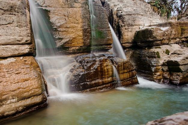 Deux rapides chutes d'eau coulant sur le rocher dans le canyon de martvili le jour de l'automne
