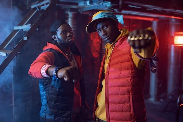 Deux rappeurs avec des bijoux en or dans un studio cool, décoration underground. artistes de hip-hop, chanteurs de rap branchés, break-danseurs