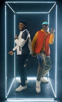 Deux rappeurs élégants pose dans un cube lumineux, studio avec fond sombre