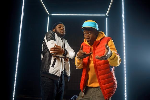 Deux rappeurs élégants posent dans un cube lumineux, avec un fond sombre. artistes hip-hop, break-danseurs