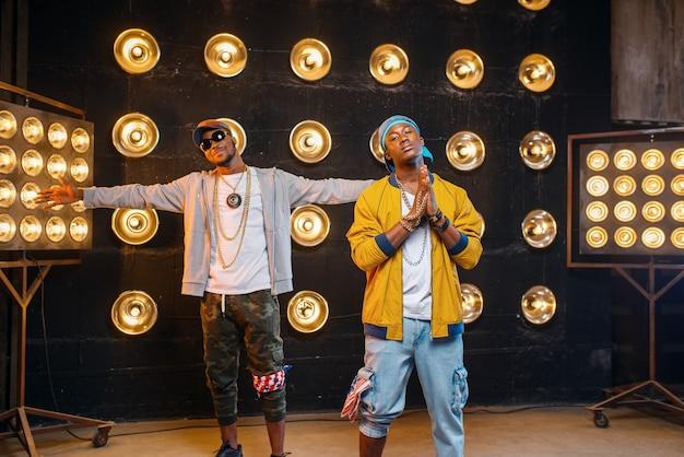 Deux rappeurs noirs en casquettes, des artistes posent sur scène