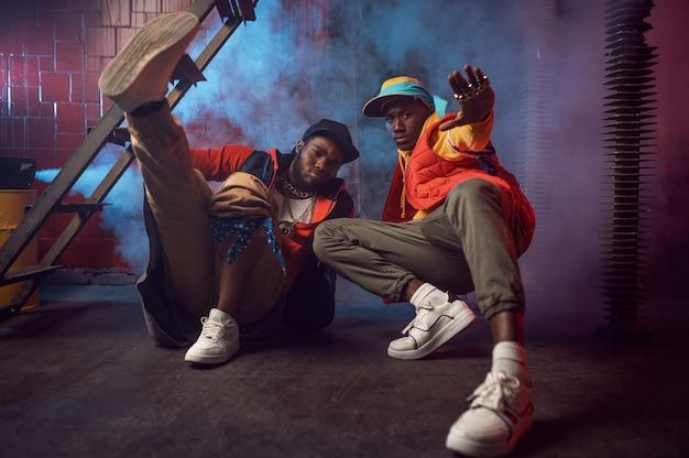 Deux rappeurs sérieux avec des poses de bijoux en or, décoration underground. artistes de hip-hop, chanteurs de rap branchés, break-danseurs