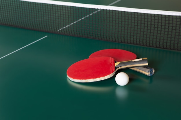 Deux raquettes de ping-pong et une balle sur une table verte. filet de ping-pong.