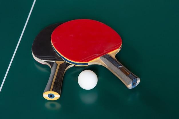 Deux raquettes de ping-pong et une balle sur une table verte.
