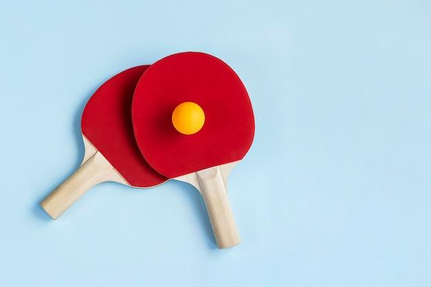 Deux raquettes de ping-pong rouges et balle sur fond bleu clair concept de mode de vie actif