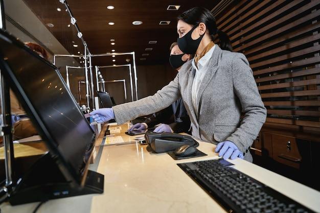 Deux réceptionnistes debout derrière le bouclier de verre sur leur lieu de travail et portant des gants en caoutchouc et des masques médicaux