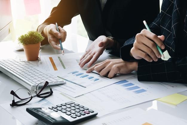 Deux responsables d'équipe travaillant sur des documents comptables et une équipe travaillant ensemble