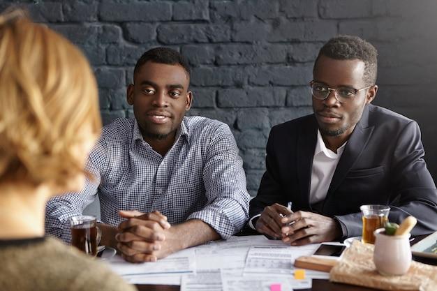 Deux responsables des ressources humaines africains confiants et prospères interrogent une jeune candidate lors d'un entretien d'embauche