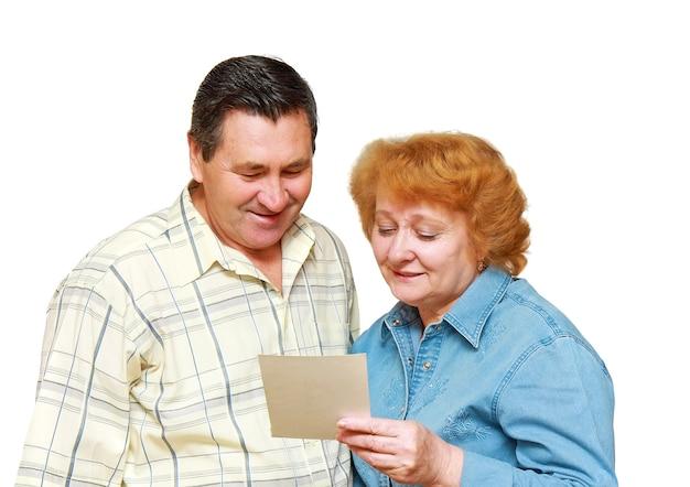 Deux retraités, en couple, regardent la photo de famille avec joie. isolé.