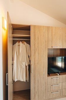 Deux robes blanches à l'intérieur d'un placard avec une porte ouverte et une niche sous une télévision à écran plasma