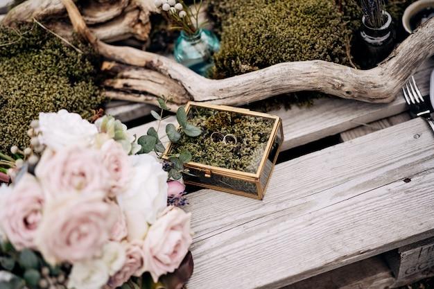 Deux robes de mariée avec une boîte à bijoux en miroir sur des planches en bois avec un bouquet de roses roses
