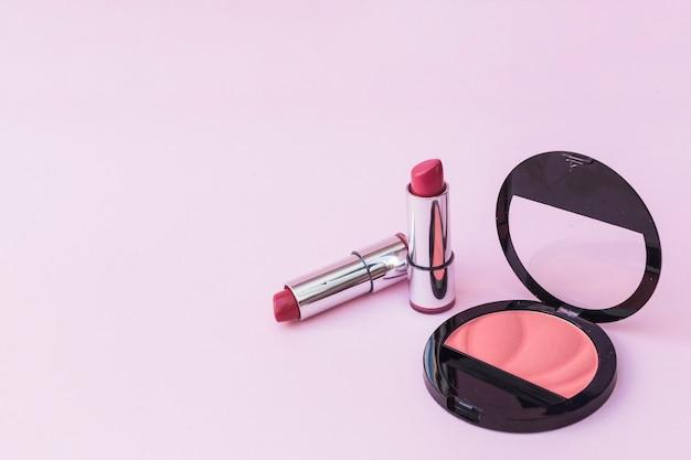 Deux rouges à lèvres et fard à joues rose sur fond rose