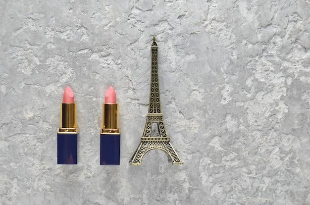 Deux rouges à lèvres roses et une statuette de la tour eiffel. vue de dessus.