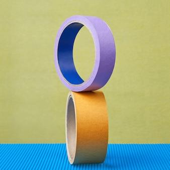 Deux rouleaux de ruban adhésif coloré sont équilibrés.
