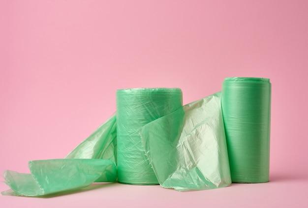 Deux rouleaux de sacs en plastique vert pour poubelle sur surface rose
