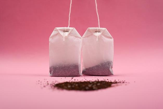 Deux sacs en papier avec du thé et avec un tas de thé noir en vrac sur un gros plan de fond rose.