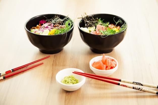 Deux salades poke avec du boeuf et du thon dans un bol avec diverses sauces sur la table du restaurant salades poke