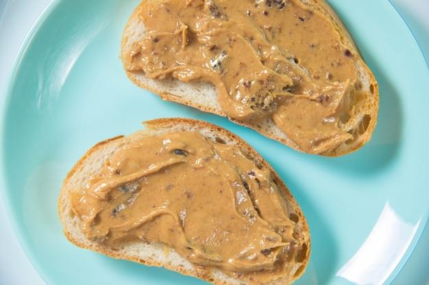 Deux sandwichs au beurre d'arachide en gros plan. le sandwich au beurre de cacahuète est dans l'assiette.