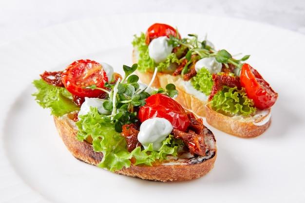 Deux sandwichs aux légumes sur une plaque blanche, avec tomate, laitue, herbes, mayonnaise et sauce