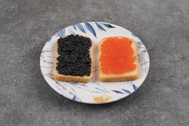 Deux sandwichs frais avec du caviar rouge et noir sur une assiette sur une surface grise