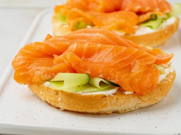Deux sandwichs ouverts avec du saumon, du fromage à la crème, des tranches de concombre sur une table en marbre blanc