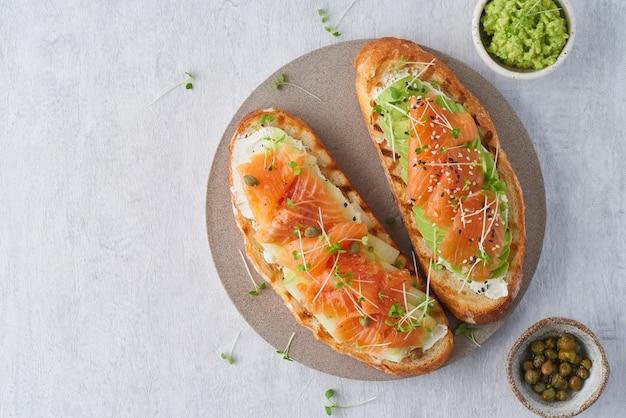 Deux sandwichs ouverts, pain grillé au saumon, fromage à la crème, avocat, tranches de concombre sur béton blanc