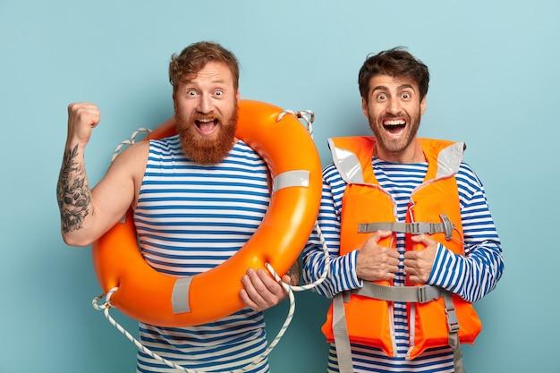 Deux sauveteurs hommes utilisent une bouée de sauvetage, portent un gilet orange spécial, regardent joyeusement la caméra