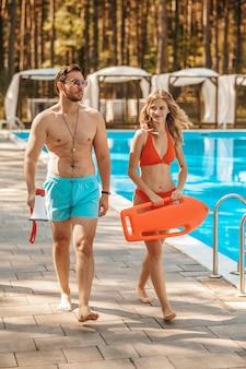 Deux sauveteurs de piscine marchant près de la piscine publique et parlant