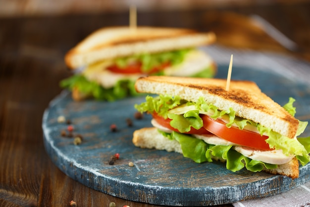 Deux savoureux sandwich au poulet, tomates, laitue, fromage sur une plaque de bois sur un fond sombre