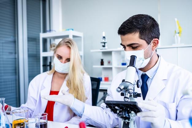 Deux scientifiques travaillent en regardant un tube à essai avec un échantillon dans un laboratoire de chimie ou de jeunes chercheurs féminins et masculins font des enquêtes dans le contexte de l'analyse de laboratoire