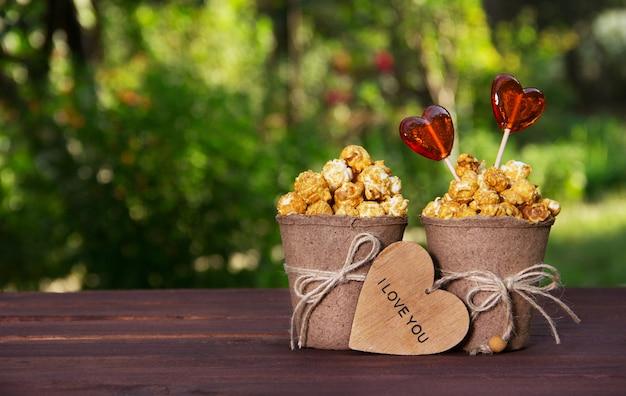 Deux seaux en papier avec pop-corn et sucettes en forme de coeur