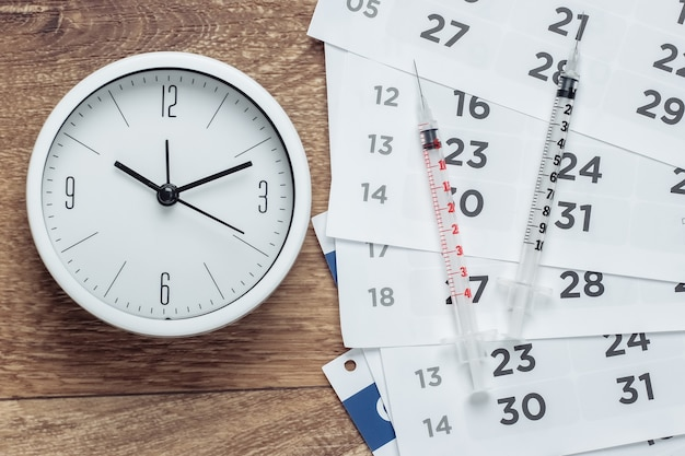 Deux seringues et horloge avec calendrier mensuel sur plancher en bois. vaccination
