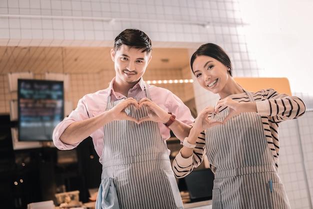 Deux serveurs. deux serveurs joyeux rayonnant portant des tabliers rayés debout près de l'entrée du restaurant