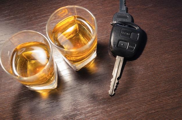 Deux shots de whisky sur le comptoir du bar avec une clé de voiture entre eux ; se concentrer sur la clé
