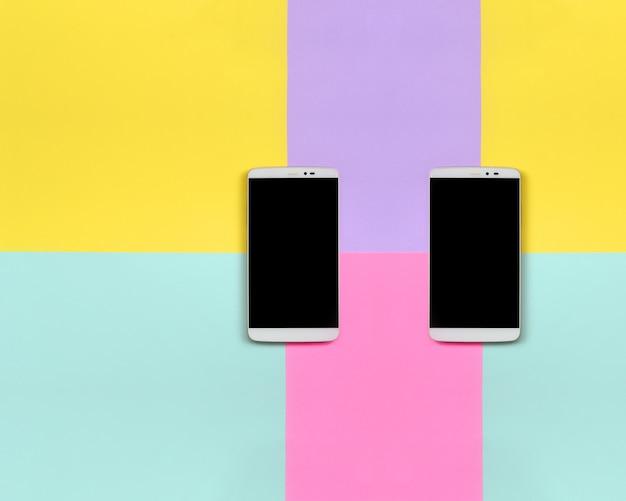 Deux smartphones modernes avec des écrans noirs sur fond de texture