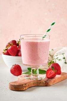 Deux smoothie aux fraises ou milk-shake aux baies et à la menthe en verre sur fond rose clair. boisson d'été shake, milkshake et concept biologique de rafraîchissement. régime alimentaire sain, concept de nourriture végétarienne.