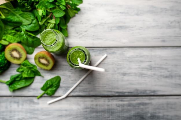 Deux smoothie aux légumes, avocat, pomme, kiwi sur un fond en bois. nutrition sportive