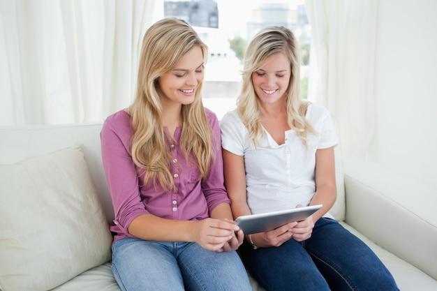 Deux sœurs assises sur le canapé alors qu'elles regardent une tablette