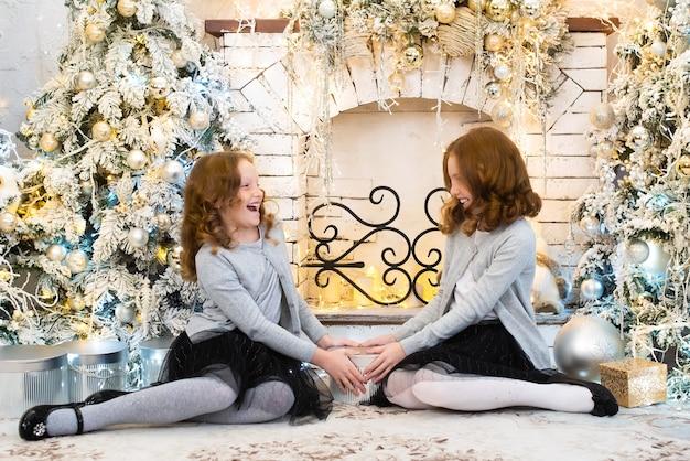 Deux sœurs aux cheveux roux près de l'arbre du nouvel an.