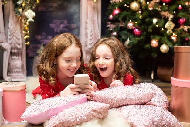 Deux sœurs aux cheveux roux près des arbres du nouvel an en regardant le téléphone noël