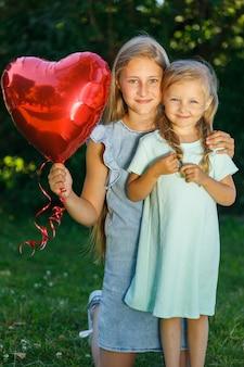Deux sœurs avec un ballon en forme de coeur