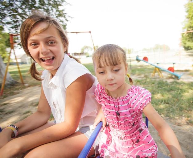 Deux soeurs sur le carrousel au terrain de jeu