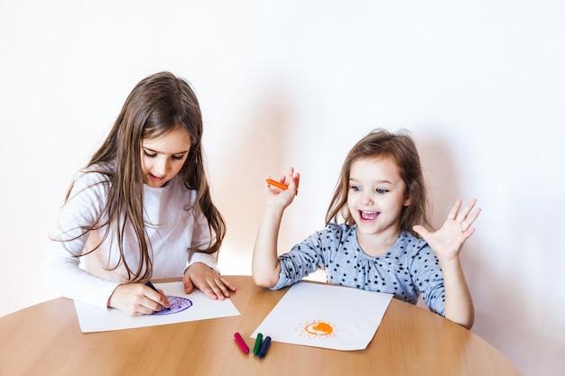 Deux soeurs dessinant avec des crayons sur une feuille de papier. concept d'art créatif