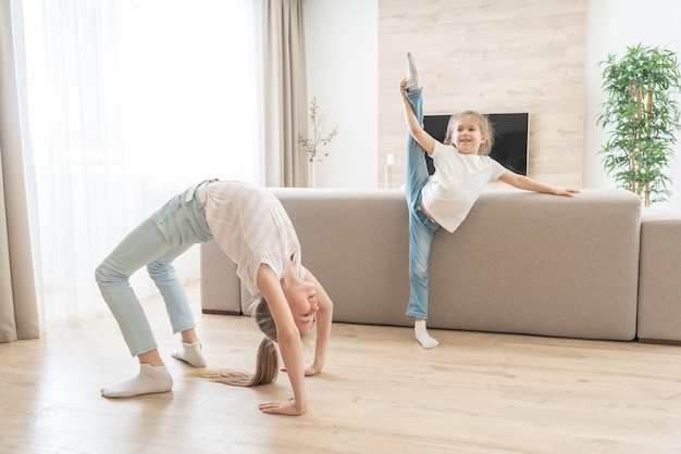 Deux sœurs faisant des exercices d'étirement de yoga dans le salon à la maison