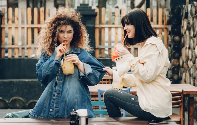 Deux sœurs faisant une pause et buvant du jus de fruits frais après un long voyage en voiture