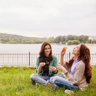 Deux soeurs gaies assis sur l'herbe et soufflant des bulles