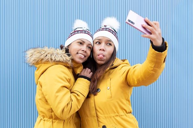 Deux sœurs avec un geste drôle et les mêmes vêtements prenant une photo avec un smartphone sur fond bleu.